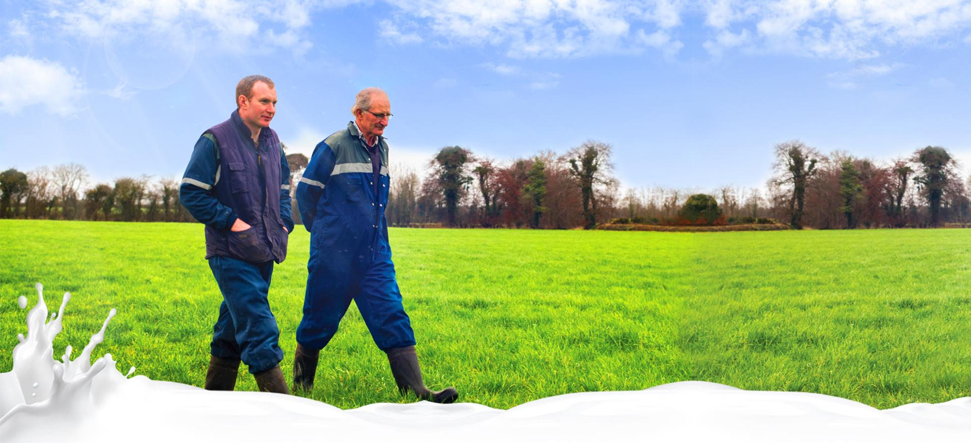 Two farmers walking through a green field