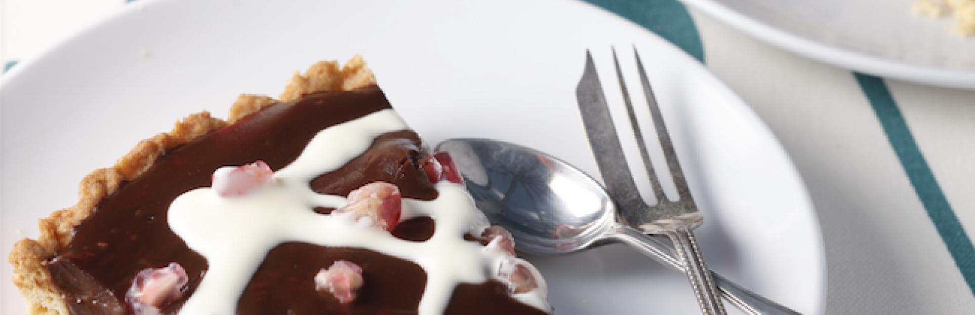 An image of a chocolate ganache tart with pomegranate seeds and a bottle of fresh dessert cream beside it