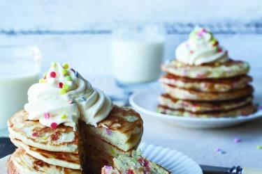 An image of two plates with pancakes covered in whipped cream