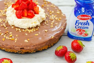 An image of a chocolate cheesecake with some avonmore fresh cream beside it