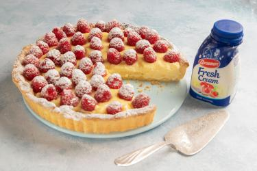 an image of frangipane fresh cream with raspberries on top